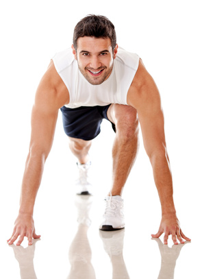 Competitive male athlete ready to run - isolated over a white background